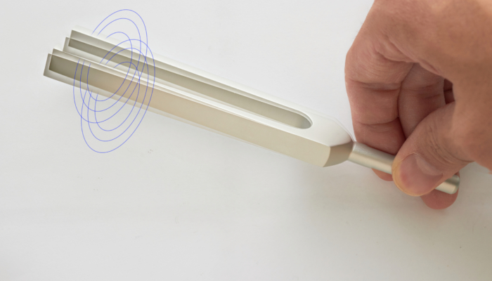 A tuning fork vibrating in someone's hand